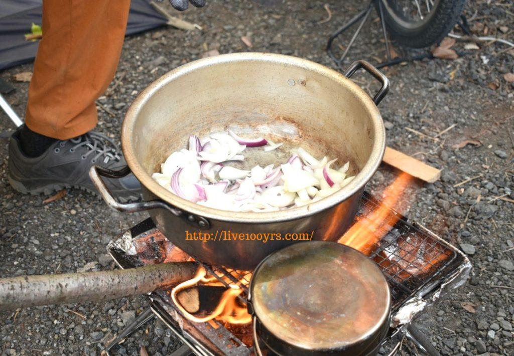 キャンプでカレー作り、たまねぎを炒め始めます