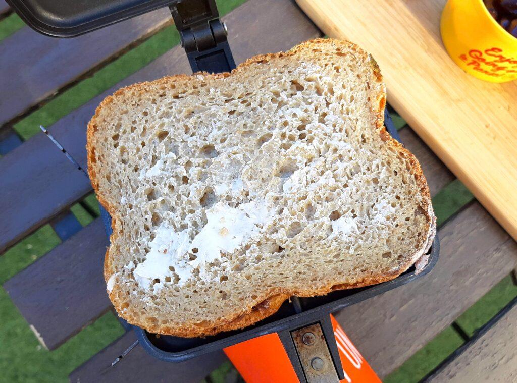ホットサンドメーカーにパンをのせて、上のパンにバターを塗ります