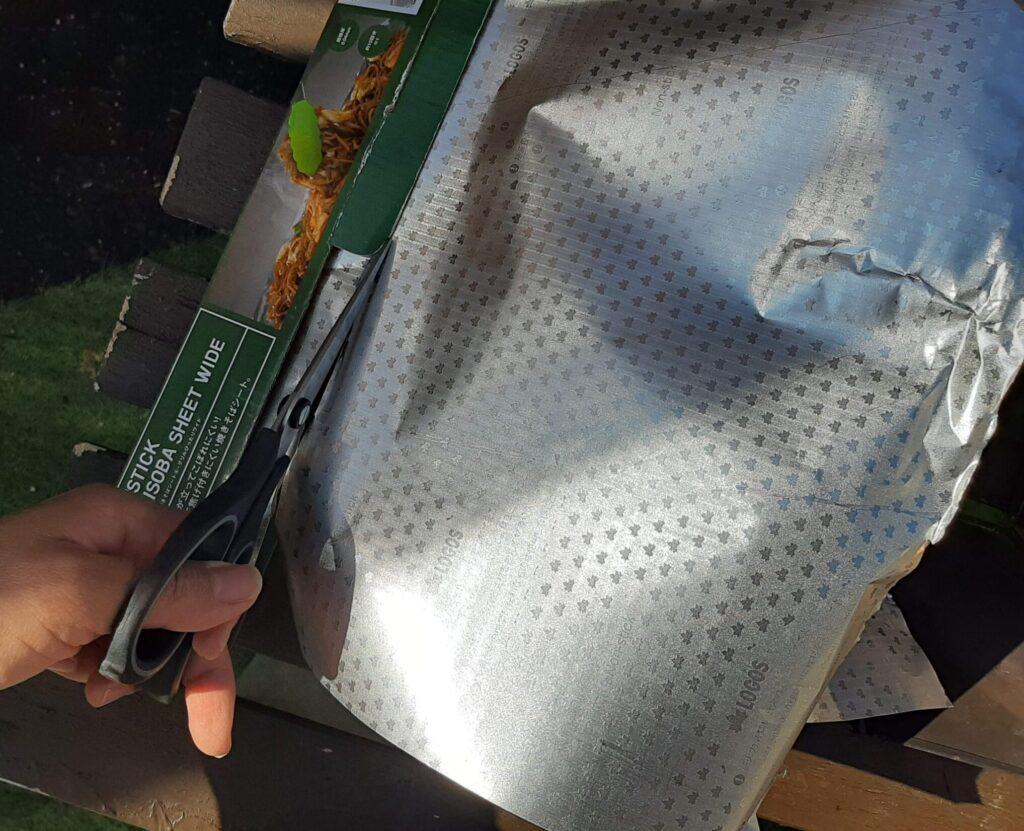 BBQお掃除楽ちんシートをはさみで切ります